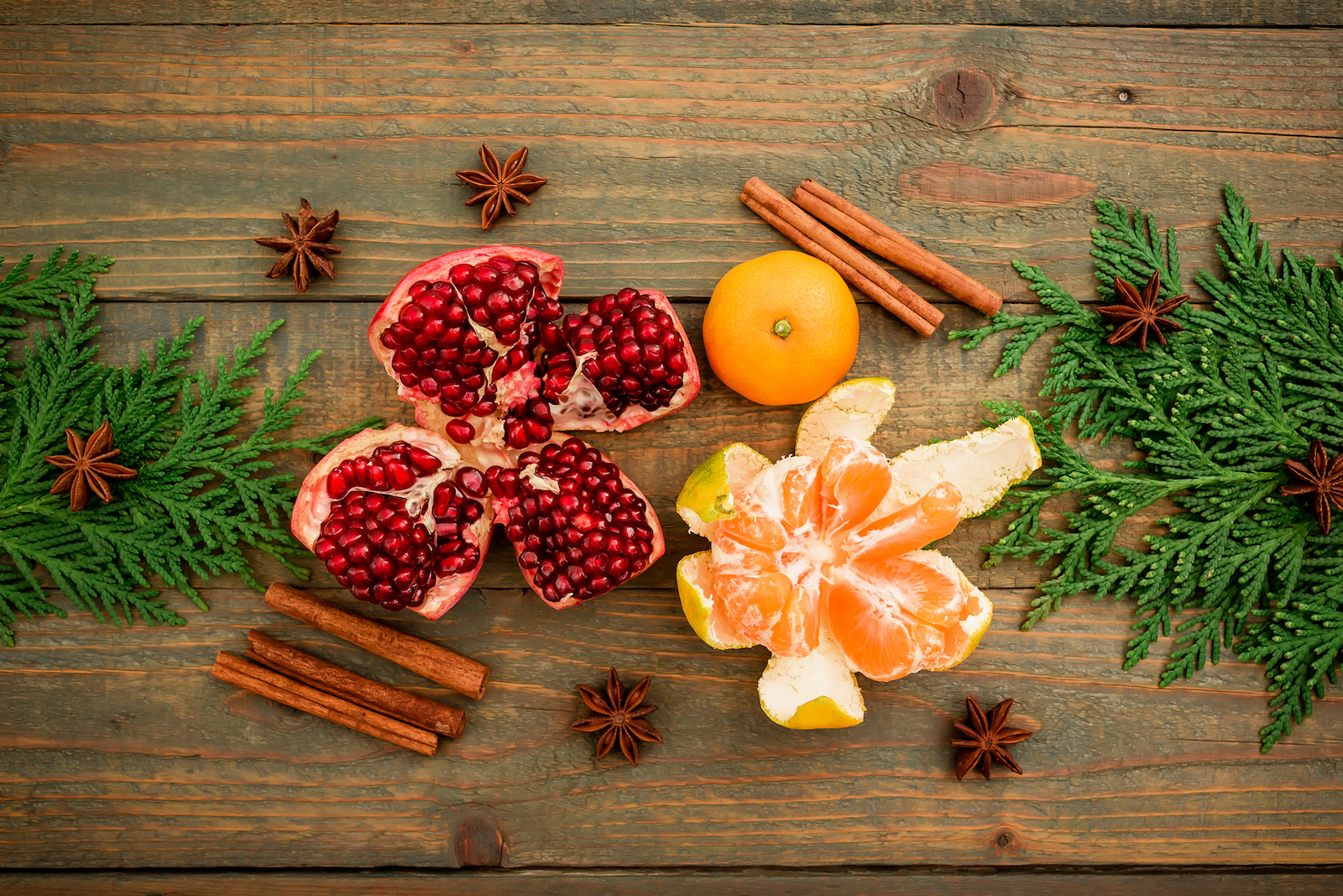 Christmas of New year concept. Fresh delicious garnet, citrus, cinnamon and anise on wooden table. Flat lay. Top view